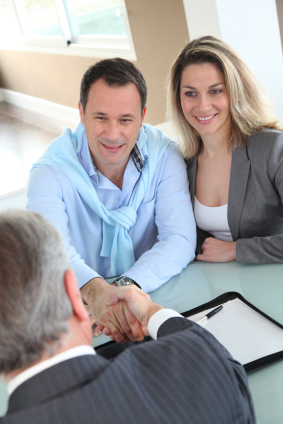 Couple shaking hands with loan officer